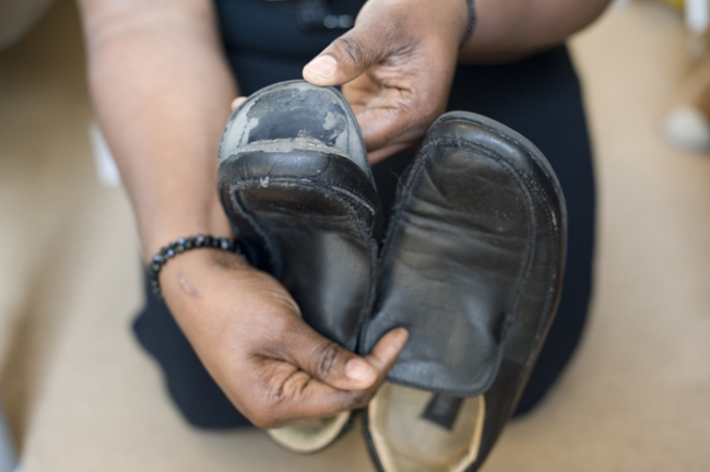 Julie Henry holding a pair of her son\'s shoes which have holes in them. She has the difficult decision of whether to buy new shoes or sending her children on a holiday. She doesn\'t want her children to be wearing shoes with holes.